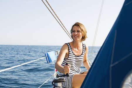 lavishly: Woman pulling rigging on boat LANG_EVOIMAGES