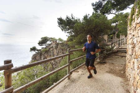 Man running on rocky coastline LANG_EVOIMAGES