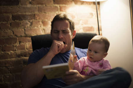 taught man: Tired father reading to baby daughter