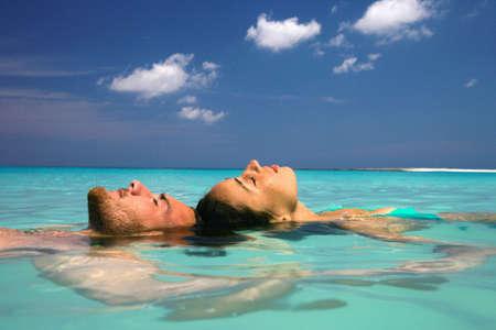 Couple floating in tropical ocean