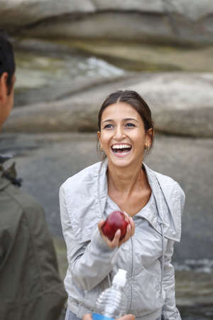 morsels: Smiling woman eating apple outdoors LANG_EVOIMAGES