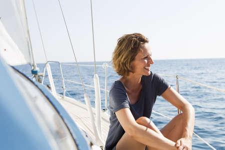 lavishly: Smiling woman sitting on boat LANG_EVOIMAGES