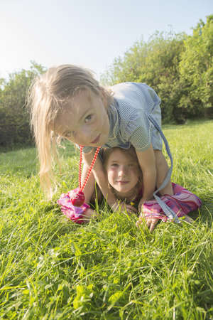 Girls playing together in grassy field