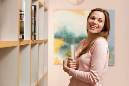 Young woman holding book by bookcase,laughing LANG_EVOIMAGES
