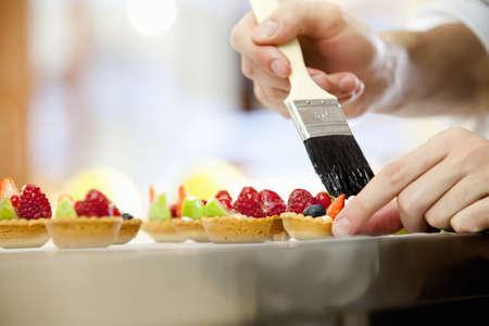 Baker glazing fruit tarts in kitchen LANG_EVOIMAGES