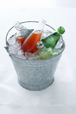 Soda bottles in bucket of ice LANG_EVOIMAGES