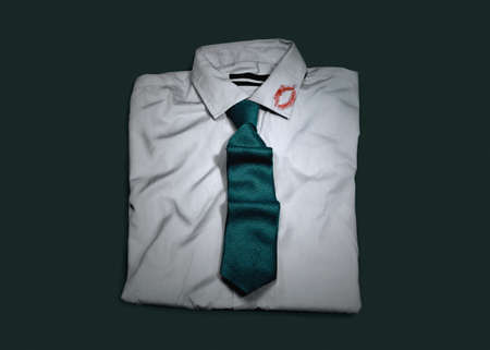 swindled: Folded shirt and tie with lipstick kiss