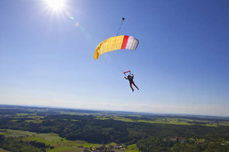 Man parachuting over rural landscape LANG_EVOIMAGES