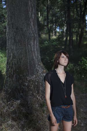 musing: Woman standing in forest LANG_EVOIMAGES