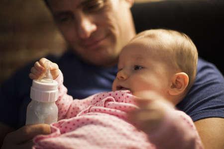 defended: Father feeding baby daughter bottle LANG_EVOIMAGES