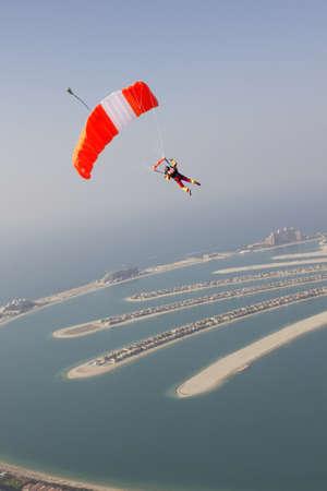 exhilarating: Woman parachuting over rural landscape