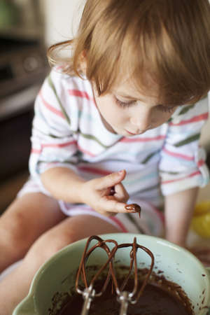 savour: Girl tasting cake batter in kitchen
