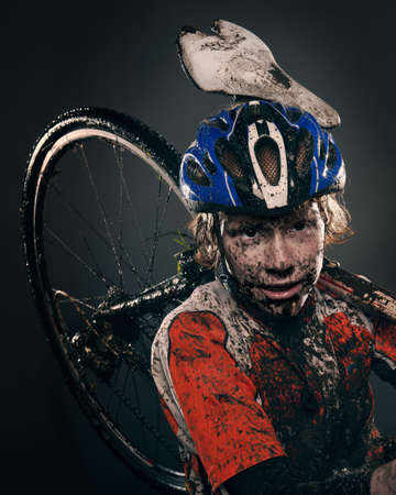 dirtied: Mud splattered cyclist carrying bicycle LANG_EVOIMAGES