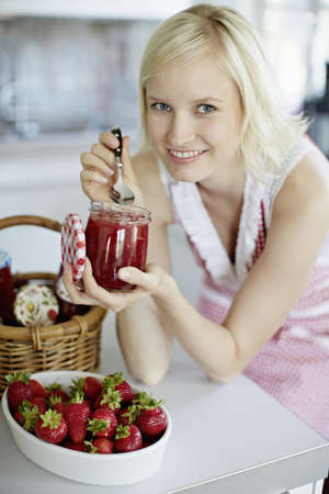 Woman eating jelly from jar in kitchen LANG_EVOIMAGES