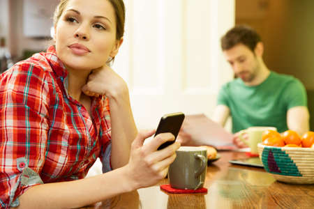 Young couple at breakfast,woman using smart phone