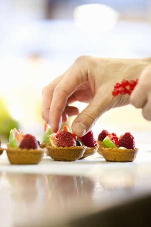 concluding: Baker making fruit tarts in kitchen