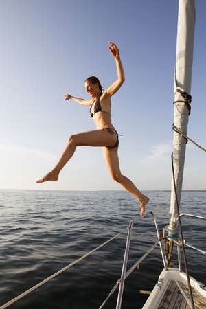 Woman jumping off boat into water