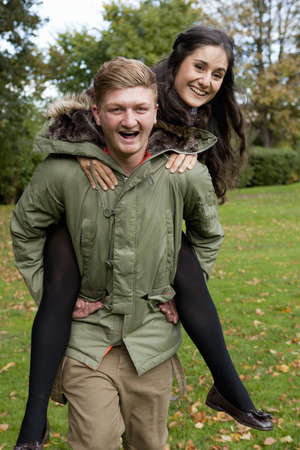 comically: Man carrying girlfriend in park LANG_EVOIMAGES