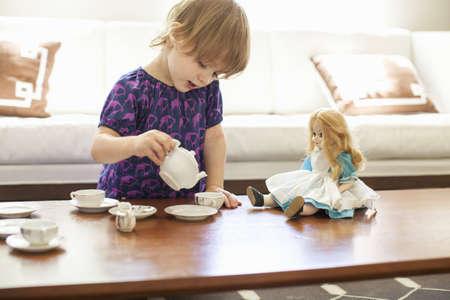 arrodillarse: Chica con una fiesta de té con muñeca