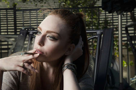 Woman smoking cigarette in lawn chair