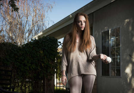 interrogations: Woman holding baseball in backyard