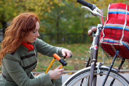 knelt: Woman locking up bicycle in park LANG_EVOIMAGES