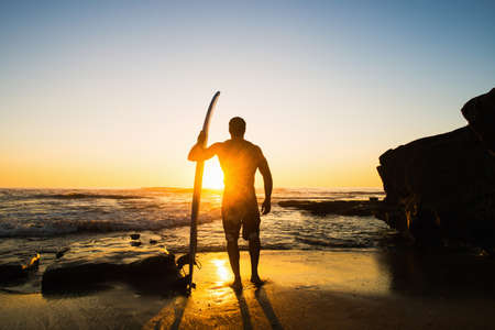 Man holding surfboard on rocky beach LANG_EVOIMAGES