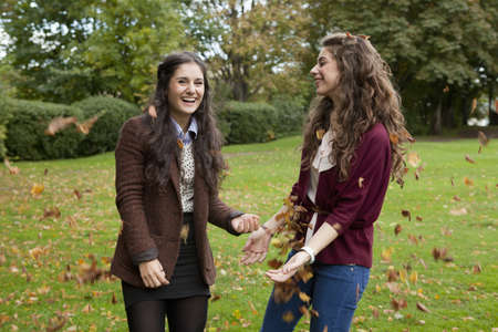 Smiling girls playing in autumn leaves