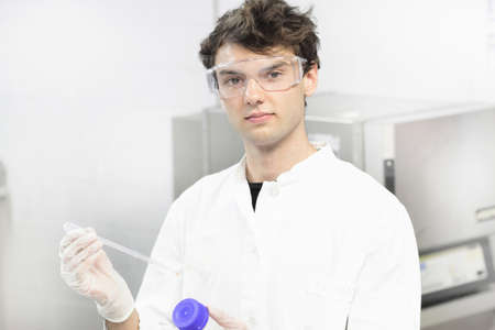 teaches: Scientist holding dropper in lab LANG_EVOIMAGES