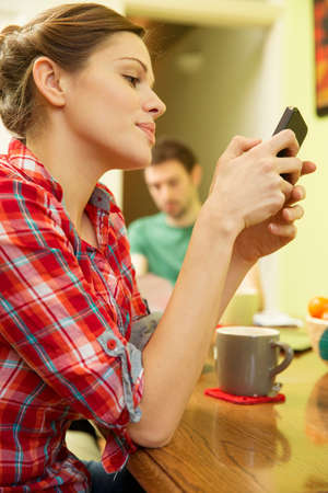tea breaks: Young couple at breakfast,woman using smart phone