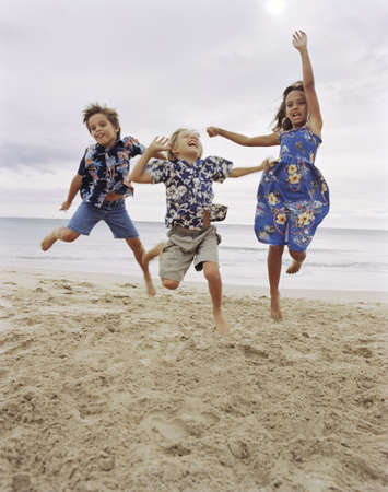 Children jumping together on beach