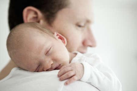 Infant sleeping on father's shoulder