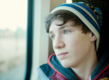 Teenage boy looking through window