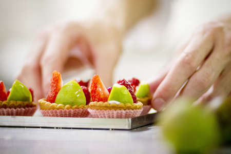 concluded: Baker making fruit tarts in kitchen