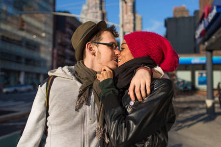 smooching: Young couple on urban street kissing