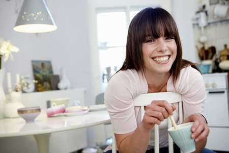 mornings: Smiling woman stirring cup of coffee