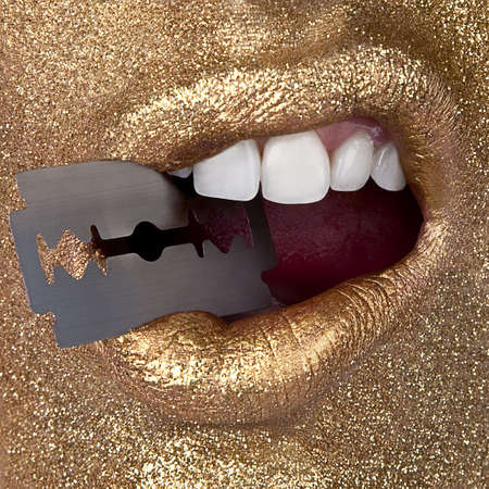 women's issues: Woman in gold holding razor in mouth