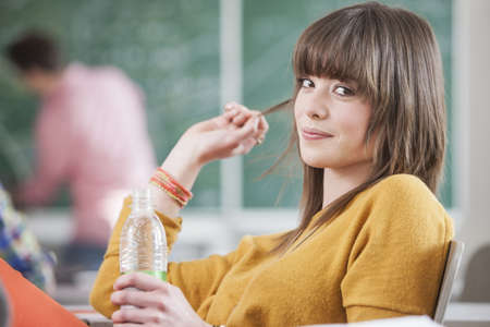 Student holding water bottle in class