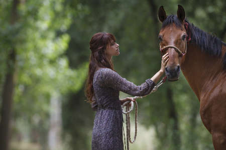 fondling: Woman walking horse in forest