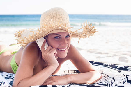 Woman talking on cell phone on beach