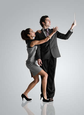 Man using digital tablet,woman reaching up
