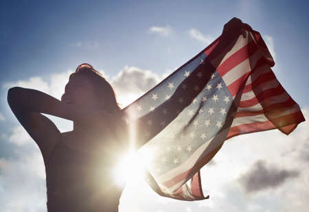 Woman holding American flag in sky LANG_EVOIMAGES