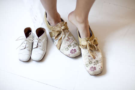antiques: Woman putting on floral shoes