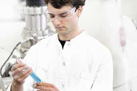 Scientist examining test tube in lab LANG_EVOIMAGES