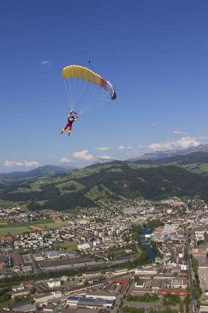 parachutists: Woman parachuting over rural landscape