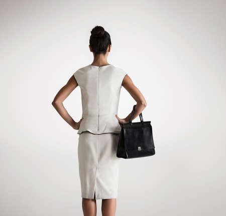 fed up: Woman holding handbag,rear view