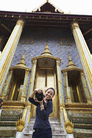 spiritual beings: Woman taking pictures at ornate temple