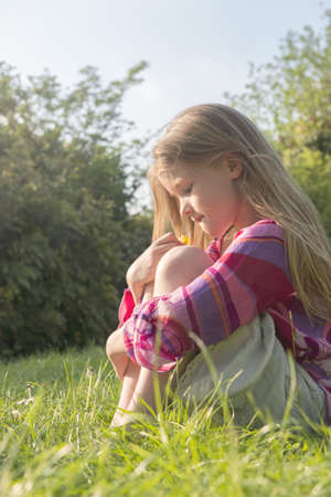 musing: Girl sitting in grassy field LANG_EVOIMAGES