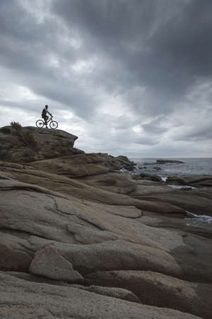 stormy waters: Man sitting on bicycle on boulder