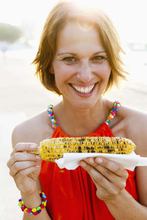 Woman eating corn on the cob outdoors LANG_EVOIMAGES